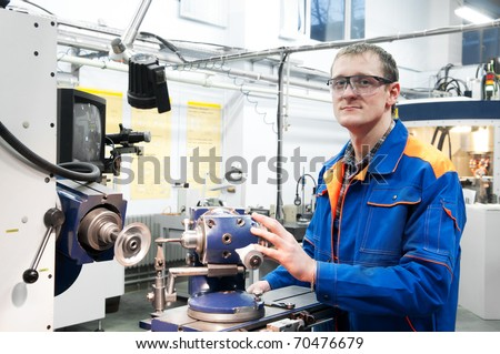worker in uniform and protective glasses sharpen countersink reamer at machine tool