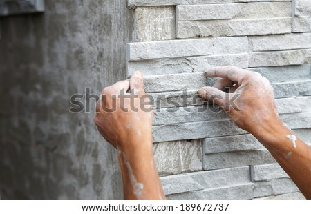 worker install stone wall surface with cement for house