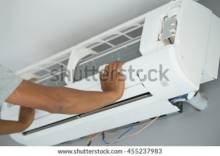 Worker installing air conditioning unit