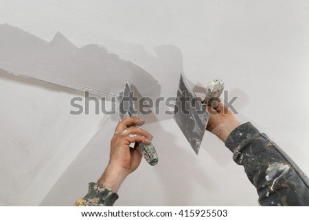 Worker spreading  plaster to wall, corner protecting batten install, repairing works