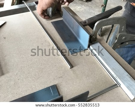 worker use measuring tape measuring length of steel on wooden table and tool on table