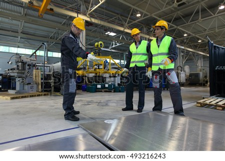 Workers working with aluminium billets at CNC machine shop