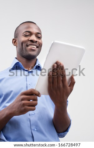 Working on digital tablet. Low angle view of handsome African man working on digital tablet and smiling while standing isolated on grey