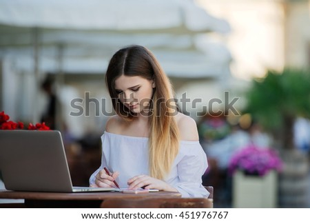 Working outdoors. Beautiful young woman working on laptop and smiling while sitting outdoors
