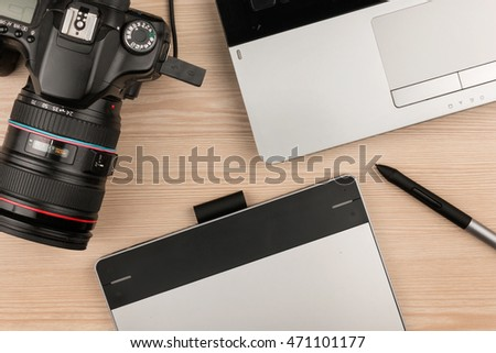 Working table of photographer or artist overhead view, wooden surface with laptop and camera
