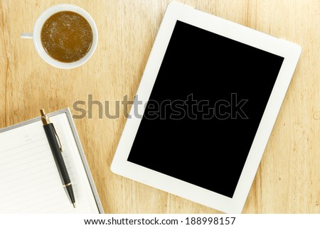 Workplace with blank digital tablet,notebook, pen and cup of coffee on work table top view