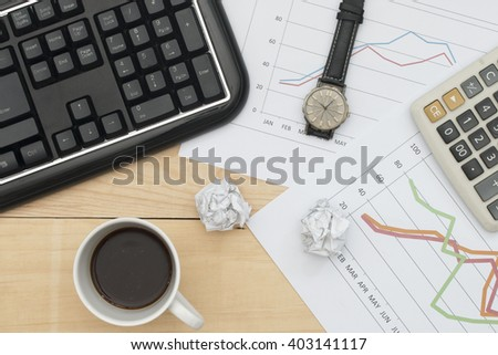 Workplace with keyboard, graph, calculator, wristwatch, and coffee on wood table.