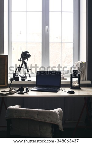 Workplace with open laptop with black screen  on modern wooden desk, angled notebook on table in home interior, filtered image. Photographer, camera