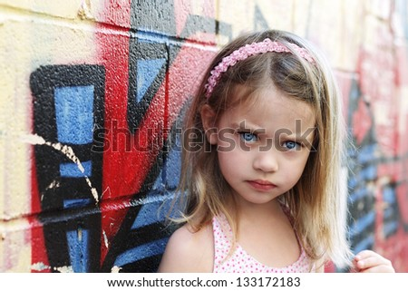 Worried little girl in an urban setting looking into the camera.