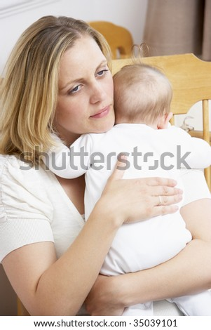 Worried Mother Holding Baby In Nursery