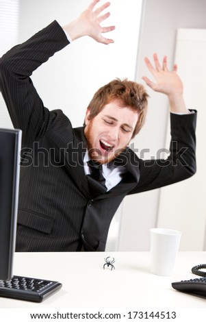Worried Young redheaded businessman crying while jumping frightened because of a little spider