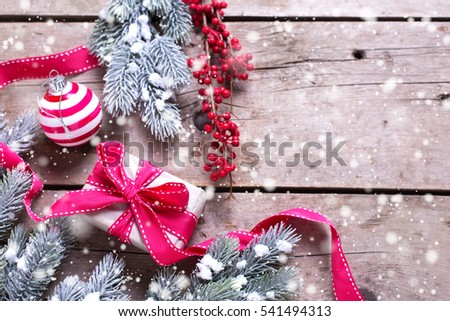 Wrapped christmas gift box, ball, red winter berries and fur tree branches on aged wooden background. Selective focus. Place for text. Drawn snow.