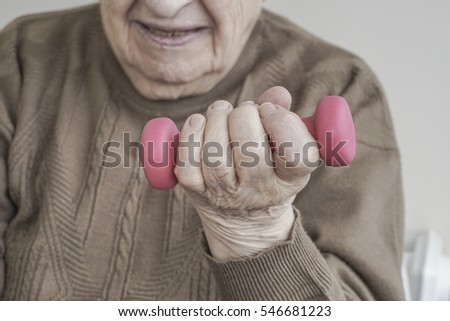 wrinkled hand of a senior woman holding dumbbell