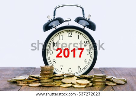 Written word 2017 on a clock with gold coins on top of a wooden table. Financial Wealth Concept.
