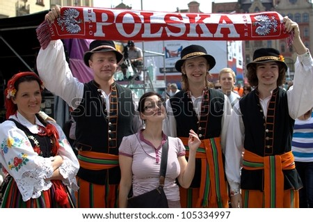 "WROCLAW, POLAND - JUNE 15:  Members of Folk Dance group ""Wroclaw"" visit Euro 2012 fanzone. Group holds Polish football neckerchief on June 15, 2012 in Wroclaw."