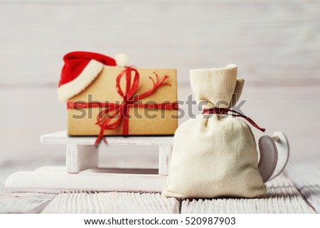 Xmas background with gift box, sledge and canvas sack