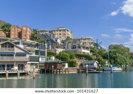 Yachts and docks at marina, with expensive houses in affluent suburb of Mosman Bay, Sydney, New South Wales, Australia