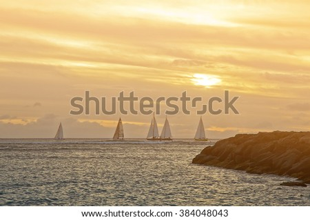 Yachts sailing past Waikiki Beach at sunset