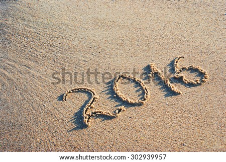 Year 2016 written in sand on a sea beach
