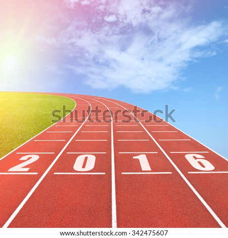 Year 2016 written on running track against sun in sky background