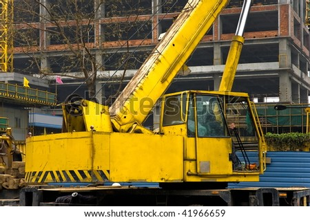 Yellow and black telescopic crane control cabin and gib arm closeup.