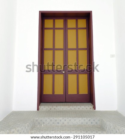 yellow and dark red color door and white wall with ceramic step