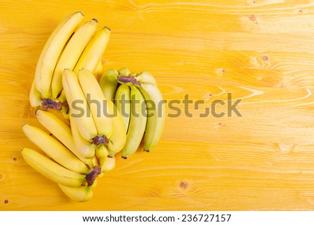 yellow and green bananas on a yellow board to the right place for your text