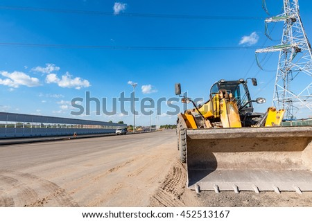 Yellow bulldozer by the new road during construction process.