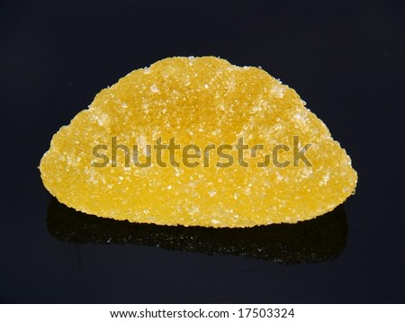 Yellow jelly candy on a reflective black background