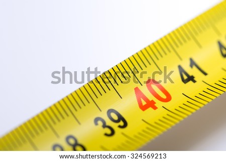 Yellow metal tape measure over white.