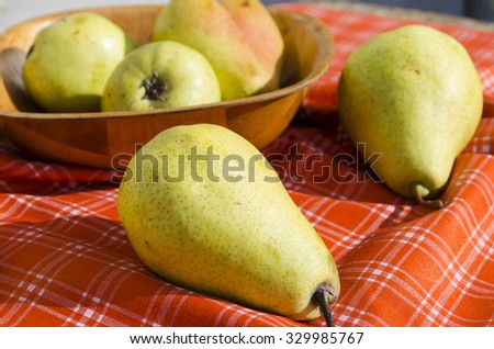 yellow pears on a red tablecloth