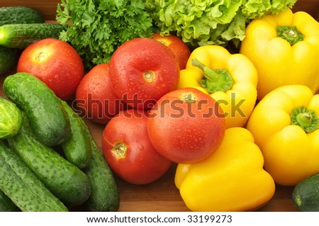 Yellow peppers, tomatoes, cucumbers, lettuce and parsley in wooden tray.