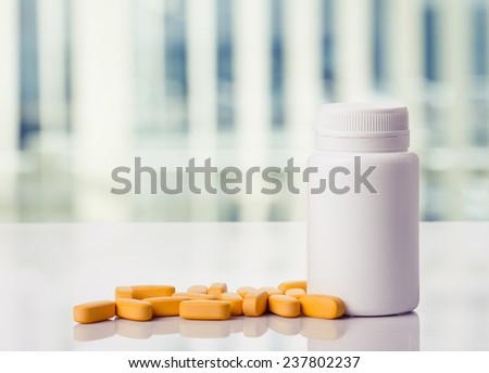 Yellow pills and pills bottle on a white table,toned photo.