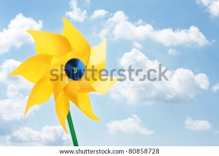 Yellow pinwheel toy against cloudy sky