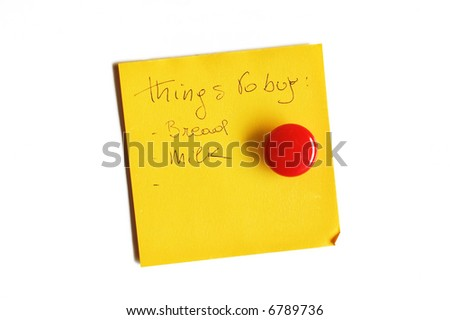 Yellow post-it isolated on white with round red magnet and handwritten message