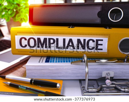 Yellow Ring Binder with Inscription Compliance on Background of Working Table with Office Supplies and Laptop. Compliance Business Concept on Blurred Background. 3D Render.