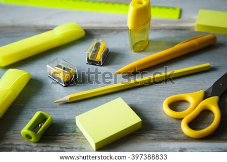 Yellow set stationery objects on wooden table copy space close up