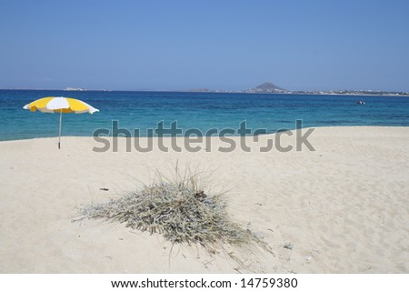 Yellow sunshade on the white greek beach of Mikri Vigla, Naxos, Greece