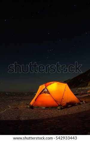 Yellow tent at night on the shore of lake Baikal in winter.