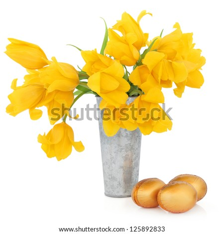 Yellow tulip flower arrangement in an aluminium vase with gold chocolate easter eggs over white background.