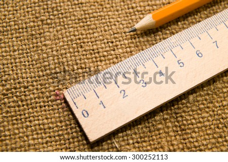Yellow wooden pencil for drawing and wooden ruler on the old tissue