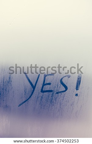 Yes written on foggy window background. Positive agreement sign