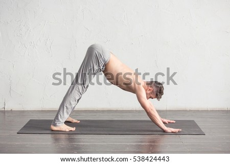 Yoga. A Young Strong Man Doing Yoga Exercises. Studio Shot Over White Wall  Background