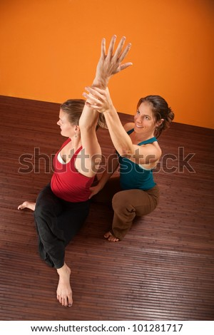Yoga coach helping student stretch shoulders