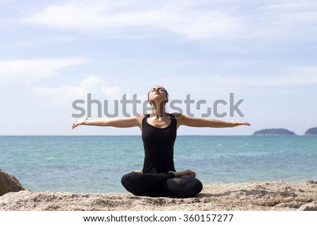 Yoga woman poses on beach near sea and rocks. Phuket, Thailand