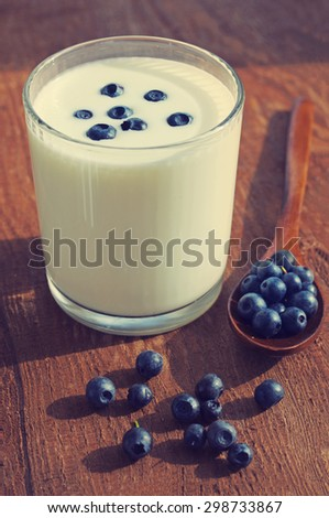 Yogurt with  fresh blueberries and blueberry in a wooden spoon on a textural brown surface