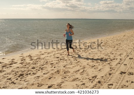 Yong pretty woman in sport outfit runs on sandy beach with dumbbells in hands and clouds in background