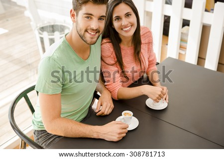 Youg couple at the local coffee shop drinking a coffee
