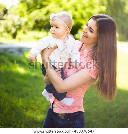 Youmg happy woman playing with her cute baby in summer sunny park outdoor. Mothercare picture