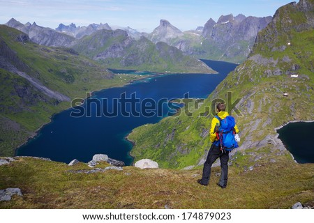 Young active man with backpack hiking on Lofoten islands in Norway on sunny day with scenic panorama in the background
